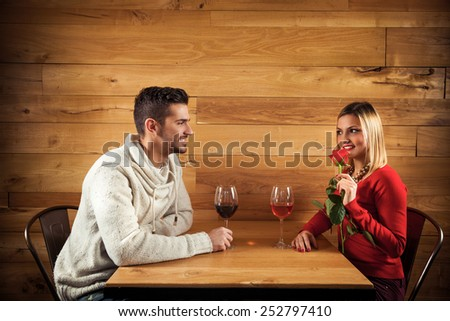 Young couple sitting in a restaurant having romantic dinner - stock photo