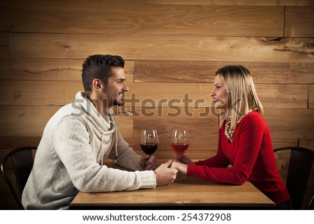 Young couple sitting in a restaurant, holding hands and drinking wine - stock photo