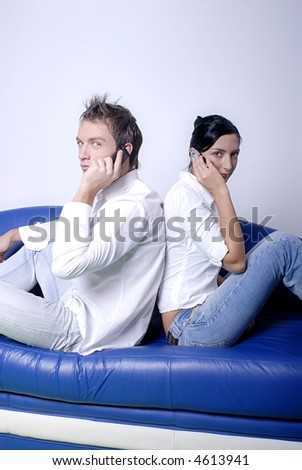 Young couple sitting in a sofa using a mobile phones