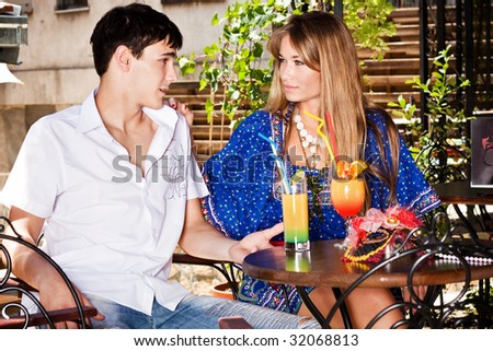 young couple sitting in cafe, outdoor summer day - stock photo
