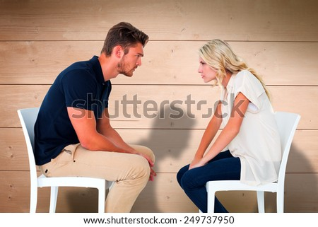 Young couple sitting in chairs arguing against overhead of wooden planks - stock photo