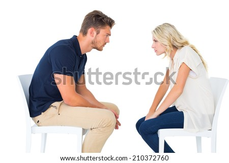 Young couple sitting in chairs arguing on white background - stock photo