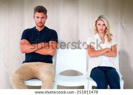 Young couple sitting in chairs not talking during argument against wooden planks - stock photo