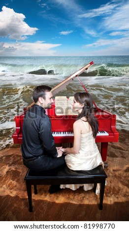 Young couple sitting in front of the red grand piano and looking at each other. Piano standing on the beach near the ocean with waves and blue sky at the background
