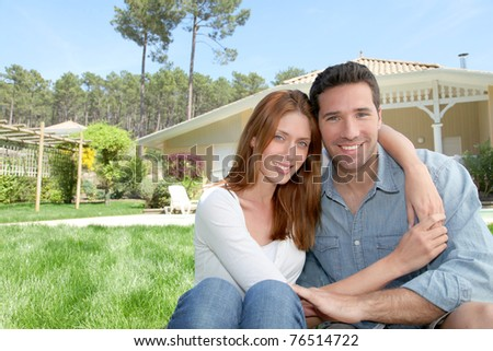 Young couple sitting in front of their new house - stock photo