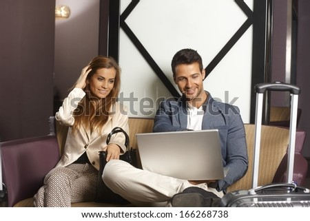 Young couple sitting in hotel lobby, using laptop computer, smiling. - stock photo