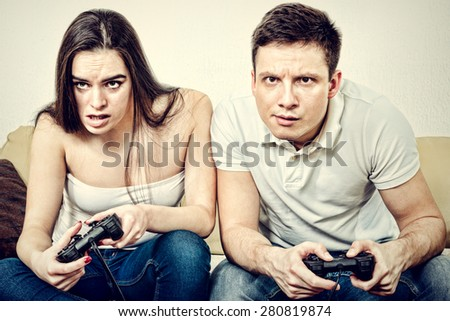 Young couple sitting in living room and play video games on console or pc with joysticks while looking in screen or TV. Lifestyle photo of man and woman in jeans at home having fun or entertainment. - stock photo