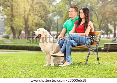Young couple sitting in park with a dog on a wooden bench - stock photo