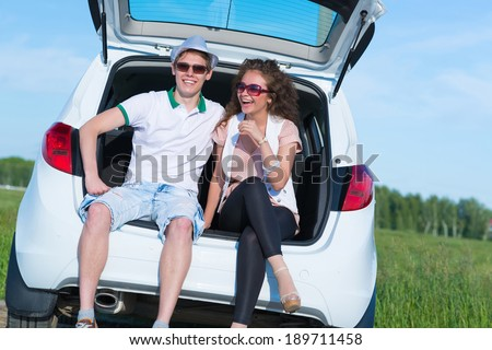 young couple sitting in the open trunk of a new car, a summer road trip