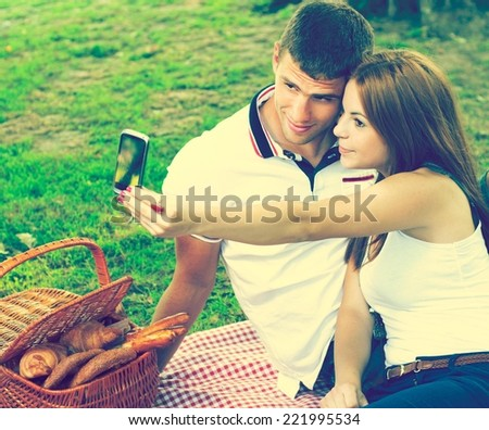 Young couple sitting in the park on a summer day. Picnic basket in the background. Taking picture of themselves with the phone.. - stock photo