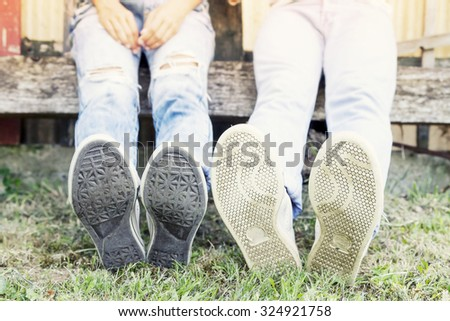 young couple sitting in the park with his feet foreground - stock photo