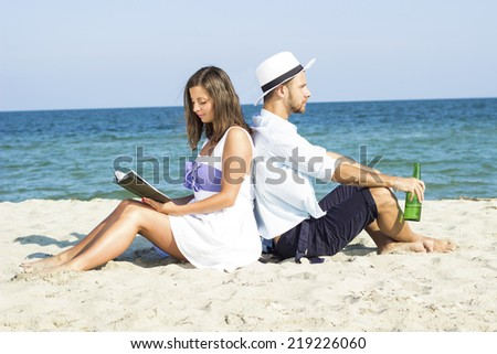 Young couple sitting in the sand on the beach leaning on each other. A woman reads a book a man drinking beer. - stock photo