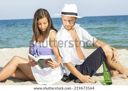 Young couple sitting in the sand on the beach leaning on each other. Women and men together read the book - stock photo