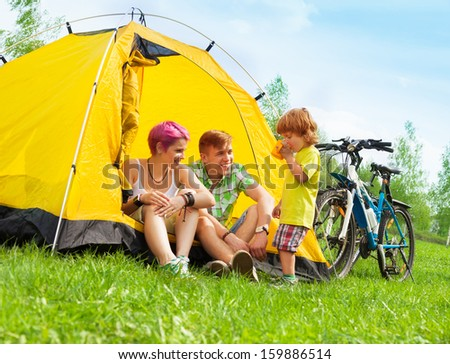 Young couple sitting in the tent with little boy drinking tea with bikes standing near - stock photo