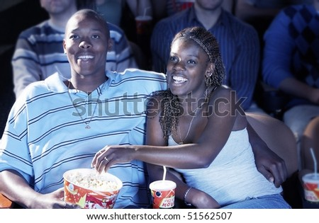 Young Couple sitting in theatre, arms around, Watching Movie, eating popcorn - stock photo