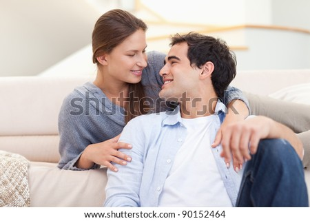Young couple sitting in their living room while looking at each other - stock photo