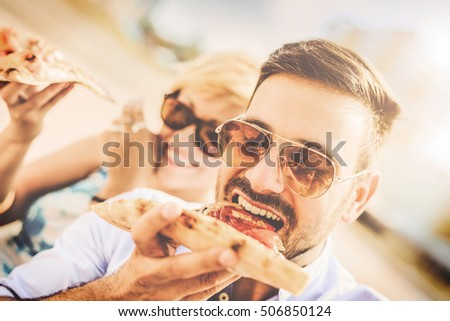 Young couple sitting on a bench in the city park and eating pizza