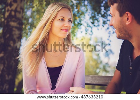 Young couple sitting on a bench in the park and talking.