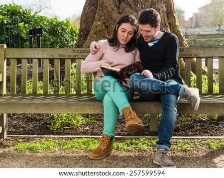 Young Couple Sitting on a Bench Reading a Book - stock photo