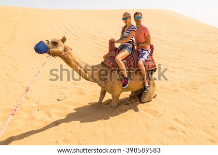 Young couple sitting on a camel in a desert. Great holidays.
