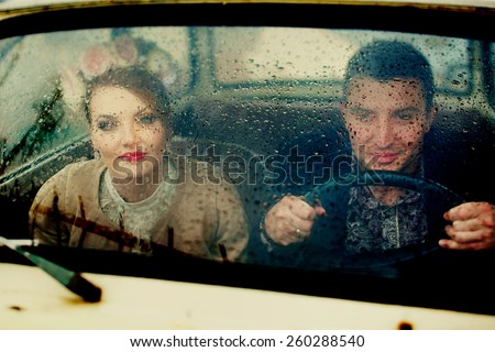 young couple sitting on a car window in the rain - stock photo