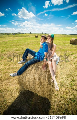 Young couple sitting on a hay stack - stock photo