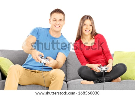 Young couple sitting on a modern sofa and playing video game isolated on white background - stock photo