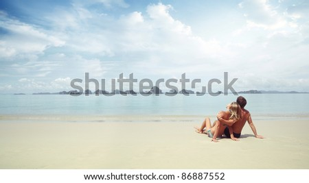 Young couple sitting on a resort's fine sand and looking to a sea - stock photo