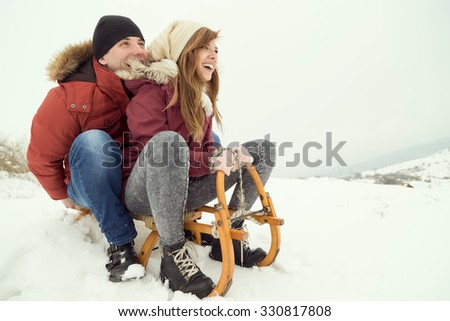 Young couple sitting on a sleigh, enjoying winter holidays - stock photo