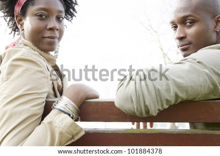 Young couple sitting on a wooden bench, turning around to look at camera with space between them.