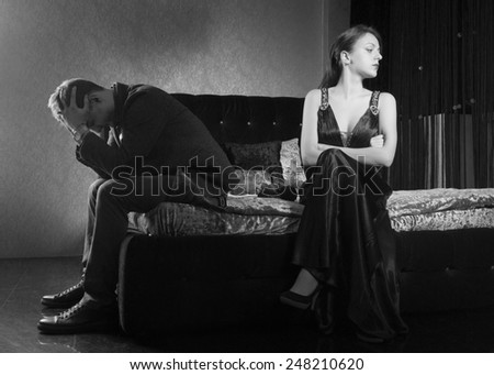 Young Couple Sitting on Bed Fighting for Something. Captured in Monochrome Style. - stock photo