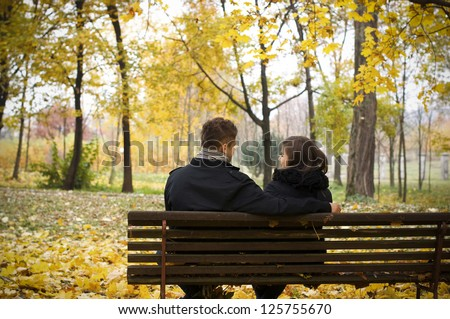 Young couple sitting on bench in park - stock photo