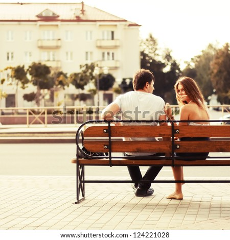 Young couple sitting on bench in park. Rear view. - stock photo