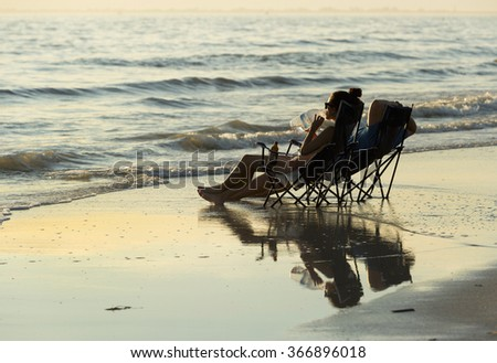Young couple sitting on chairs on the beach, watching golden sunset on the beach in Fort Myers Beach on the west coast of Florida.