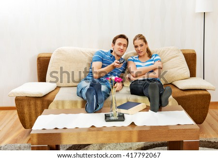 Young couple sitting on couch and watching TV