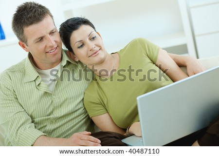 Young couple sitting on couch at home and using laptop computer. - stock photo