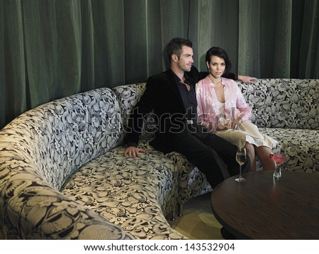 Young couple sitting on couch with drinks on coffee table in hotel lobby - stock photo