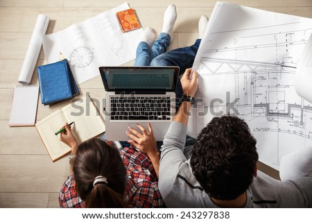 Young couple sitting on floor and  calculating about they savings.They plan to invest in new house.View from above. - stock photo