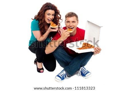 Young couple sitting on floor and enjoying yummy pizza