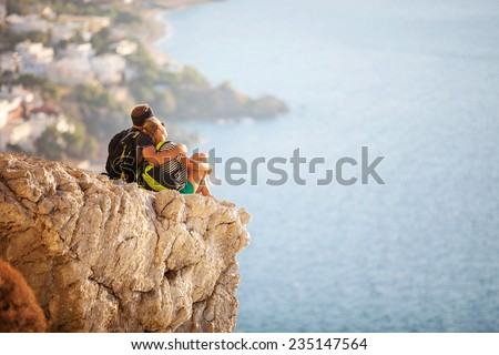 Young couple sitting on rock and enjoying beautiful view. Kalymnos Island, Greece.  - stock photo