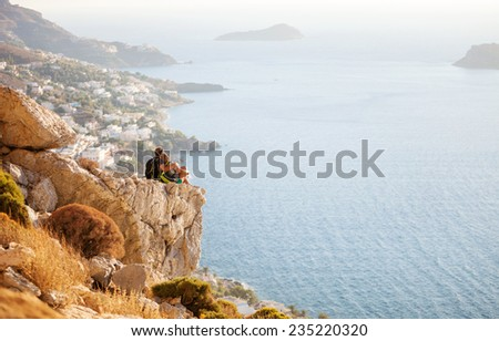 Young couple sitting on rock and enjoying beautiful view. Kalymnos Island, Greece.  - stock photo