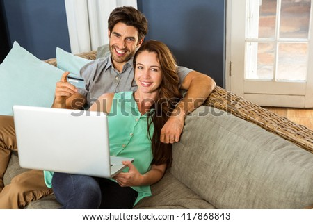 Young couple sitting on sofa and doing online shopping in living room
