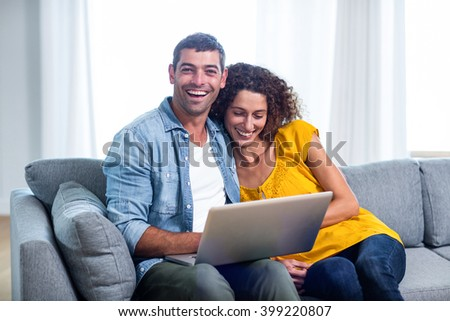 Young couple sitting on sofa and using laptop in living room