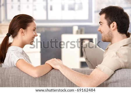 Young couple sitting on sofa at home, holding hands, smiling happily each other.? - stock photo