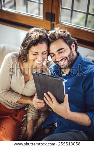 Young Couple Sitting On Sofa Using Digital Tablet - stock photo
