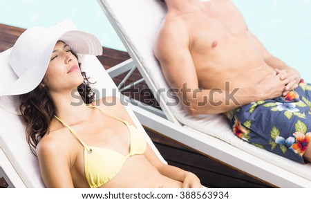 Young couple sitting on sun loungers by swimming pool - stock photo