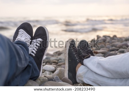 young couple sitting on the beach - stock photo