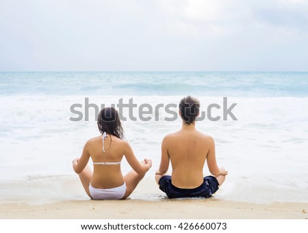 Young couple sitting on the beach in a lotus poses. Yoga training in Thailand.