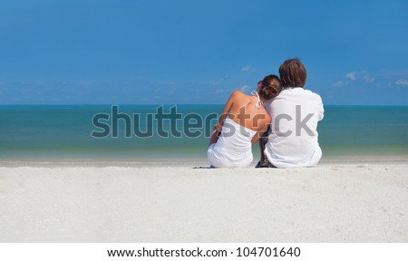 Young couple sitting on the beach looking on the horizon - stock photo