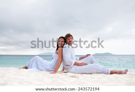Young couple sitting on the beach near the seaside